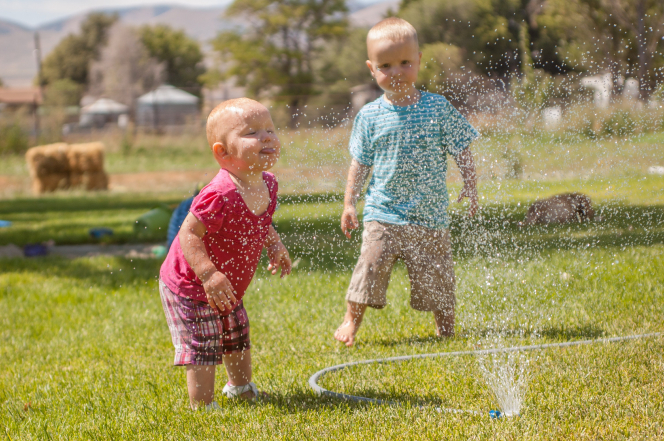 A baby puts her face in the water from a sprinkler while a toddler boy stands nearby.