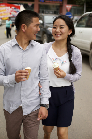 A young man and a young woman hold ice cream cones and smile at each other as they walk down a street together.