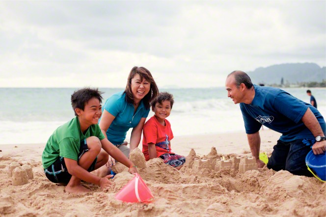 A mother smiles at the camera while her husband and two sons build a sand castle.
