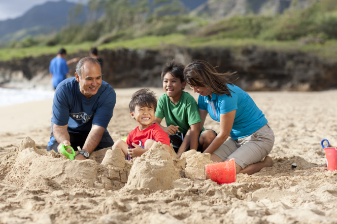 A mother and father kneel down in the sand and help their two young sons build a sand castle.
