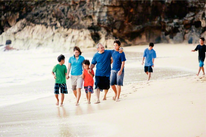 A mother and father hold hands with their three sons and walk in the sand along the beach.