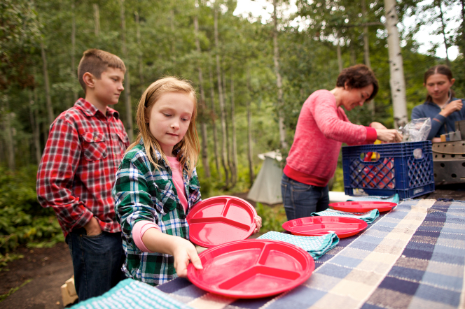A young girls sets red plates on a picnic table with her mother and siblings at a campground.