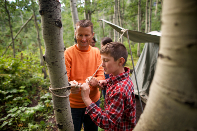 A father standing and showing his son how to tie a knot around a tree while camping in the woods.