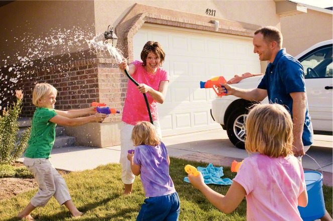 A mother sprays water on her children with a hose while the father and three children spray her with water guns in their front yard.