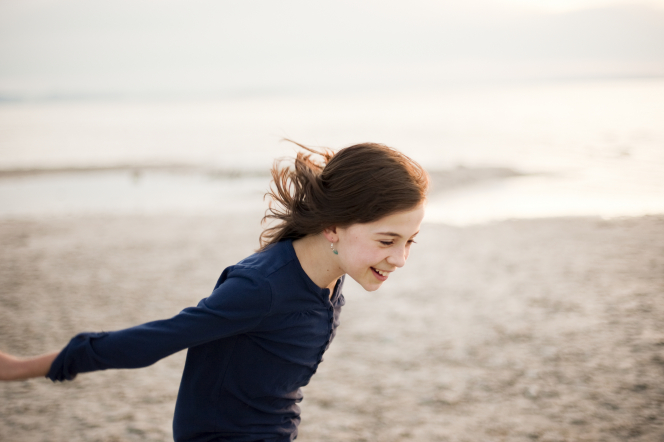 A young girl runs on the beach with her hands in the air.