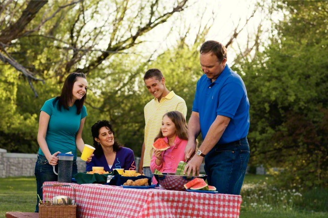 A father cuts a watermelon at a picnic table outside while the mother and their three children sit around the table.