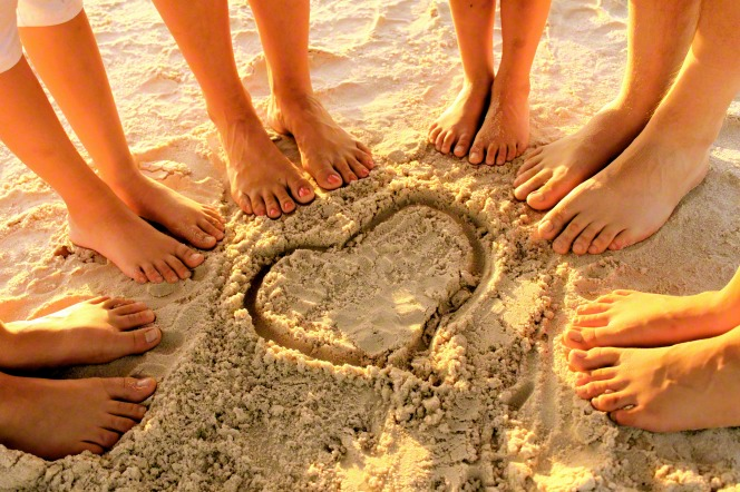 Six pairs of feet are seen standing in a circle around a heart drawn in the sand, with the sun shining in the background.