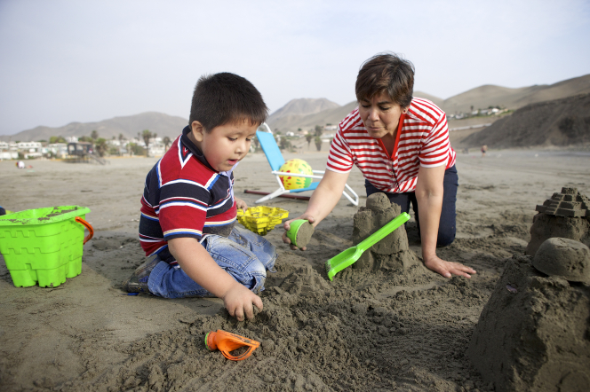 A grandmother kneels down in the sand next to her grandson and scoops up sand with him to build a sand castle.