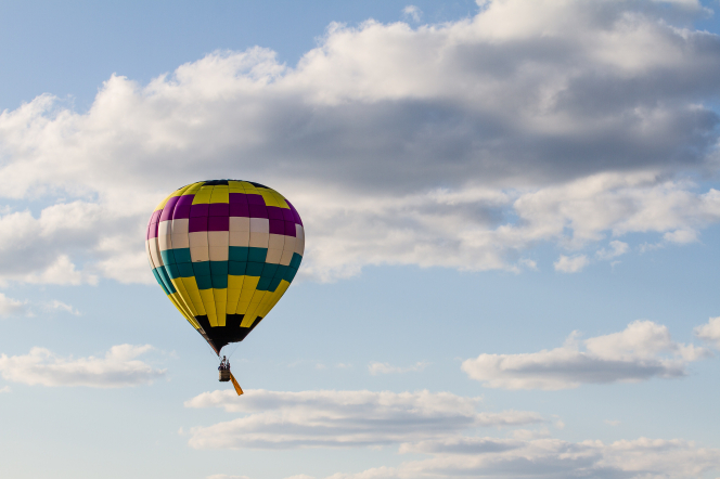 A colorful hot air balloon flies up in the blue sky, with white clouds behind it.