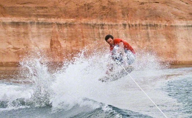 A young man holds onto a rope as he jumps a wave on a wakeboard at Lake Powell.