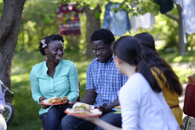 Some young adults sit in chairs in a circle outside and have a picnic together, holding plates of food on their laps.