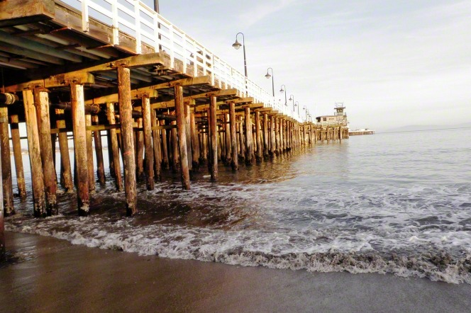 A large wooden pier with lamps and a fence on top extends out into the water, with waves crashing on the shore below.