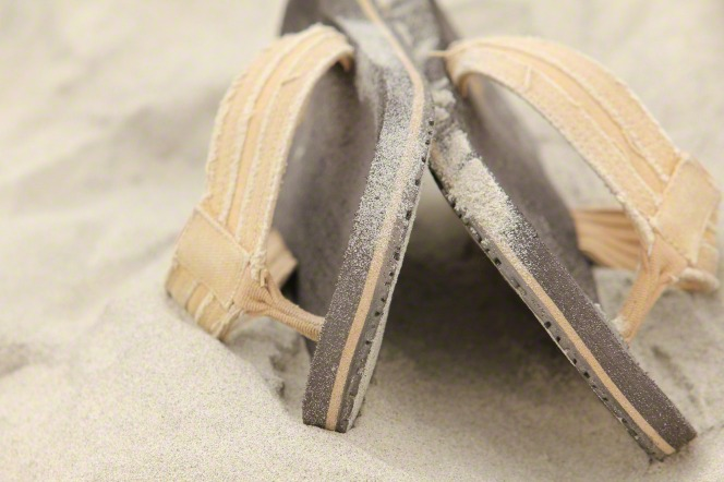 A pair of brown sandals with orange straps lying in the sand.