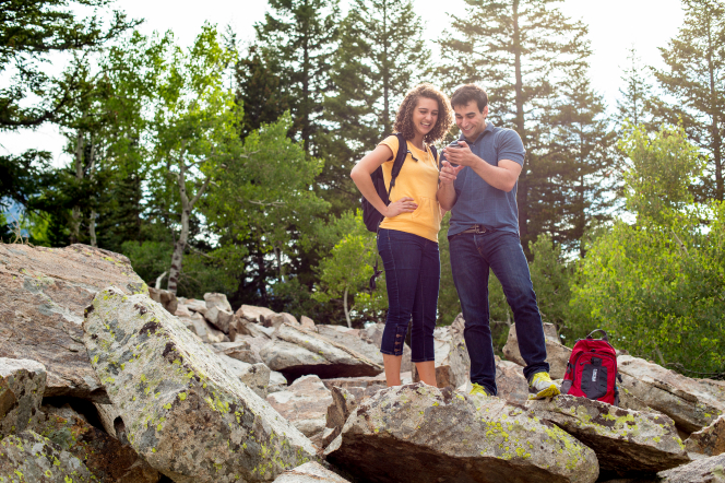 A man and woman stand on rocks and look at a phone while hiking among some trees.
