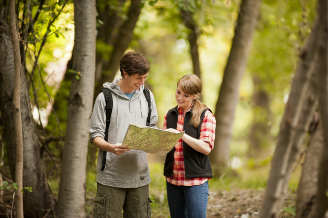 A young man holds a map and a young woman looks at it while they are on a hike in the woods.