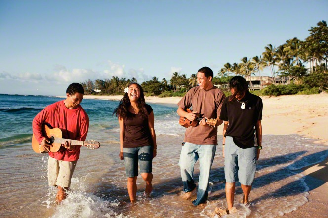A young man plays a guitar while another young man plays a ukulele, and two girls smile and walk with them in the water along the shore.