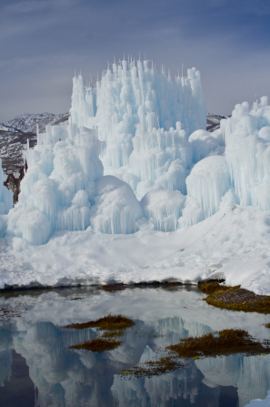 Tall ice formations reflecting in the water below, with mountains in the background in Midway, Utah.