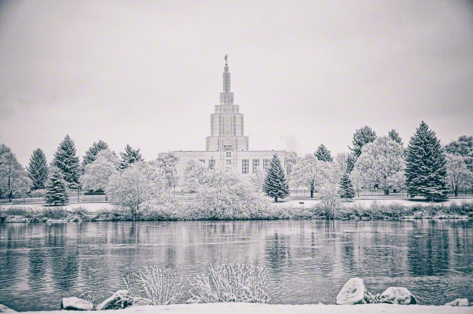 The Idaho Falls Idaho Temple and snow-covered trees reflected in the icy river.
