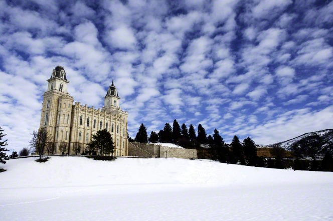 A view of the Manti Utah Temple and grounds covered in snow in winter, with a blue sky and clouds overhead.