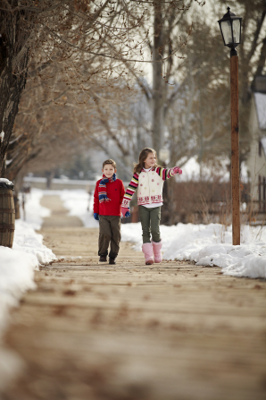 A brother and sister hold hands while walking down a sidewalk, with snow on either side.
