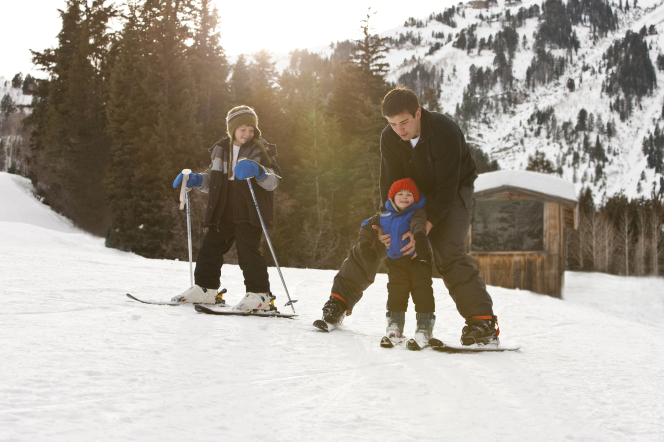 A father on skis helps push his son on skis while his other son stands next to them with skis and poles.