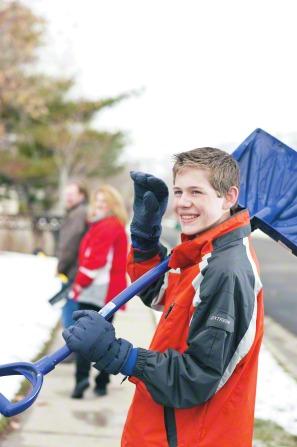 A teenage boy carries a snow shovel on his shoulder as he walks down a sidewalk.