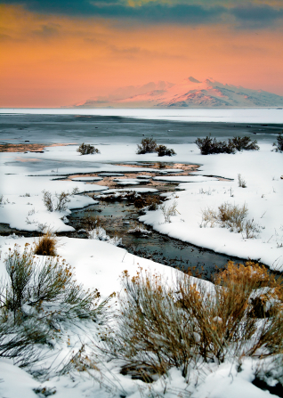 A stream runs through Antelope Island, with snow on the ground and a mountain in the background.