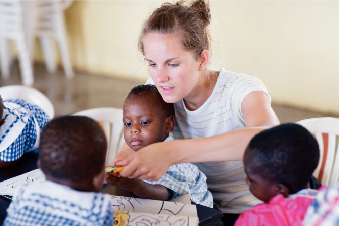 Inside an orphanage, a woman with light brown hair and a white shirt sits and holds a child while coloring pictures with other African children.