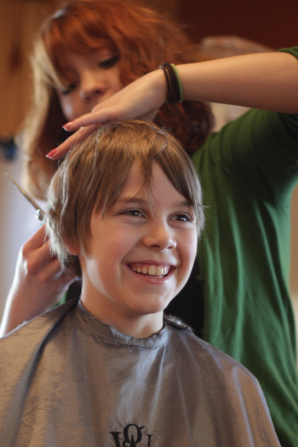 A young boy smiles while a woman stands behind him and cuts the back of his hair.
