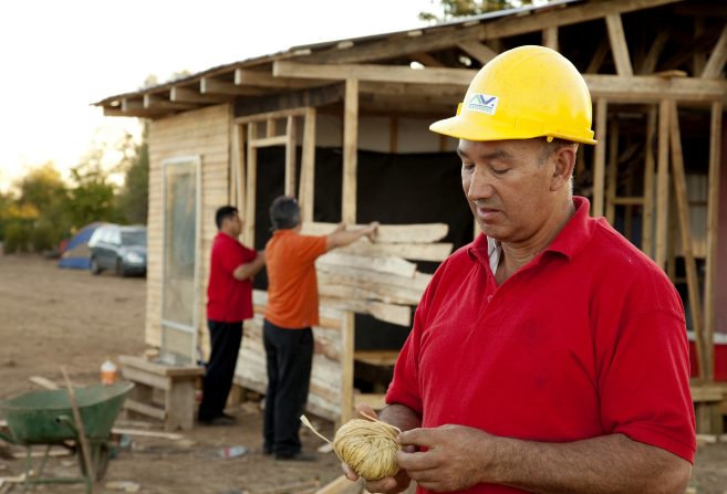 Three men, one in a hard hat, help rebuild a home after a natural disaster.