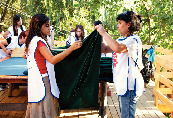 A group of women help fold blankets for Helping Hands after an earthquake in Chile.