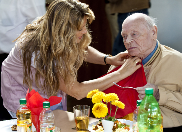 A woman leans over and helps an elderly man tuck a napkin into his shirt before he starts to eat.