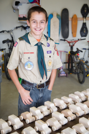 A boy in a Boy Scout uniform smiles while standing next to a group of wooden toy cars that were made for a service project.