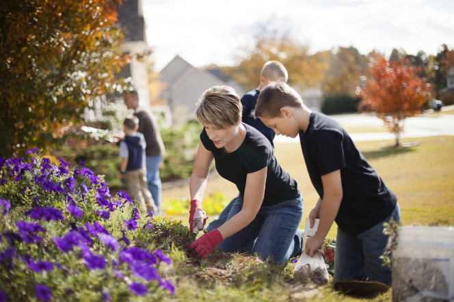 A mother and son wearing black t-shirts and blue jeans while working in a flowerbed on a sunny day with the rest of the family in the background.