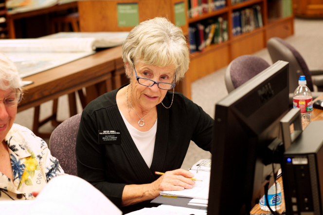 A senior Church-service sister missionary sits at a computer with other missionaries to help do research in the Family History Library.