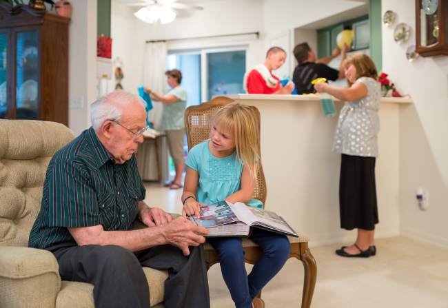 A little girl sits on a chair with a book in her lap and reads it to her grandfather, who sits in a chair next to her, while other family members clean the kitchen in the background.