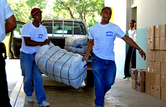 Two men unload a large package full of donated clothing from a pickup truck.