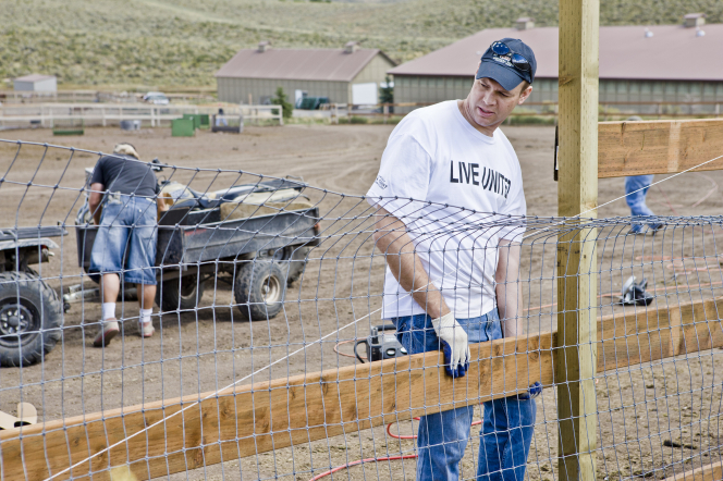 A man in a white T-shirt and blue hat puts a wooden board up to nail to a fence around a section of farmland.