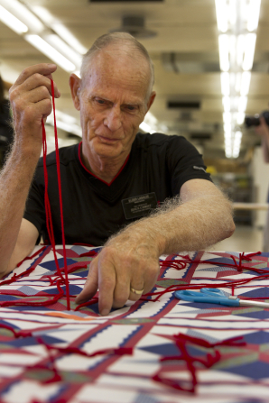 A senior missionary ties a quilt with red yarn for service at a humanitarian center.