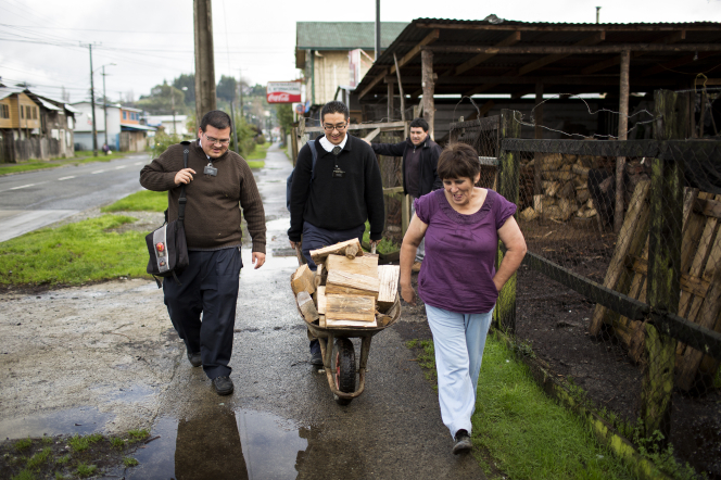 An elder and his companion push a wheelbarrow full of firewood down the street as an act of service for a woman who walks beside them.