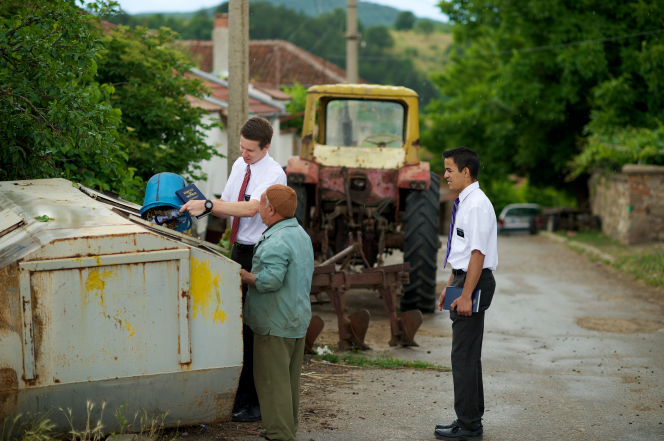 A missionary dumps a garbage can full of trash into a dumpster on a street, with an elderly woman next to him and his mission companion behind him.