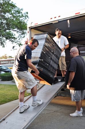 Two men carry a dresser out of a moving truck and down a ramp while another man looks on.