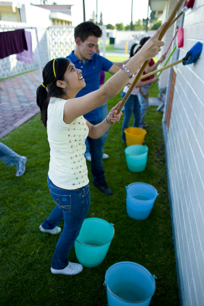 A group of youth wearing jeans and T-shirts work together to clean white walls outside with large brushes and buckets of water.