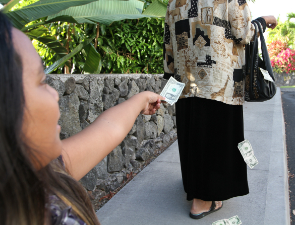 A girl holds out a U.S. dollar bill to a woman who has money falling out of her bag.
