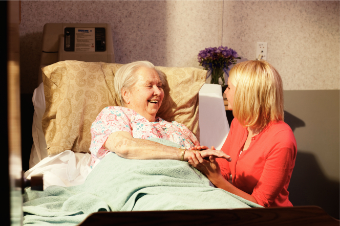 A young woman holds the hand of an elderly woman in a hospital bed.