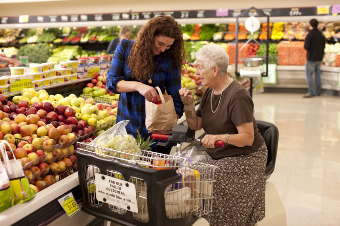 A younger woman helps put apples into a sack for an elderly woman at a grocery store.