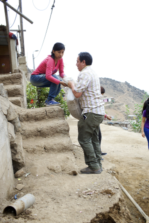 A young woman hands a bag of dirt to a young man while clearing out a home for a service project.