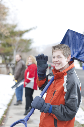 A young boy waves and smiles, carrying a snow shovel on his shoulder as he walks down the sidewalk with his parents ahead.