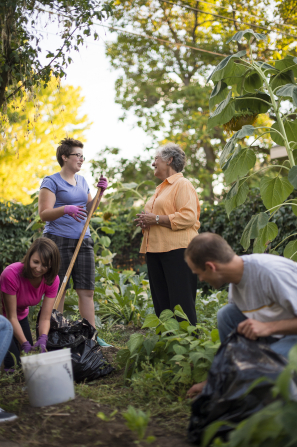 A woman holds a rake and talks to an elderly woman while a group of young adults clean up the yard.