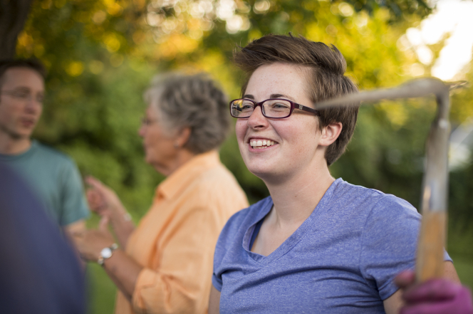 A young woman wearing glasses and a T-shirt smiles while holding a garden rake during a service project.